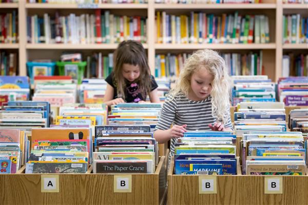 two girl students looking at books in a library