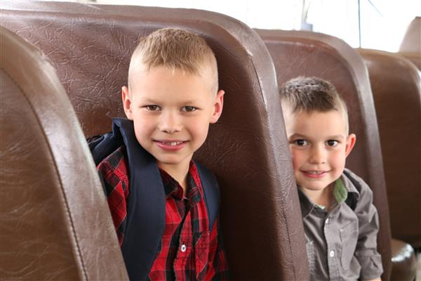 two boys wearing backpacks sitting on a bus